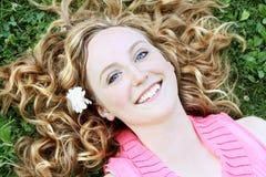Junge Frau, die in Gras legt Stockfotos