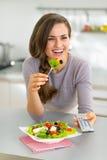 Junge Frau, die griechischen Salat isst und fernsieht Stockfotos