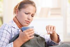 Junge Frau, die Grippe hat, ihre Temperatur zu nehmen Lizenzfreie Stockfotografie