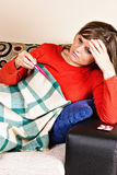 Junge Frau, die Grippe hat und ihre Temperatur nimmt Lizenzfreies Stockbild