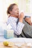 Junge Frau, die Grippe hat zu legen im niesenden Bett Stockbild