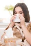 Junge Frau, die Grippe sitzt nach Hause, habend lizenzfreie stockbilder