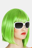 Junge Frau, die grüne Perücke über grauem Hintergrund trägt Lizenzfreie Stockfotos