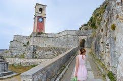 Junge Frau, die große alte Uhr in einer Festung auf Korfu-isla betrachtet Stockbilder