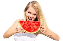 Junge Frau, die große Scheibe Wassermelonen-Beere isst Stockfotos