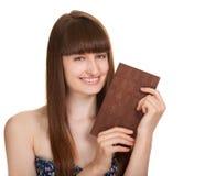Junge Frau, die großen Schokoriegel anhält Lizenzfreie Stockfotografie