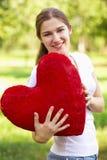 Junge Frau, die großes rotes Inneres anhält Lizenzfreies Stockfoto