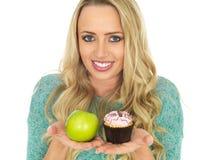 Junge Frau, die gutes und schlechtes Lebensmittel vergleicht Lizenzfreies Stockbild