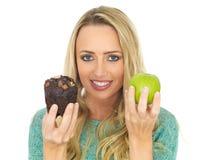 Junge Frau, die gutes und schlechtes Lebensmittel vergleicht Stockfotos