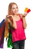 Junge Frau, die Gutscheine und Einkaufstaschen hält Lizenzfreie Stockfotos