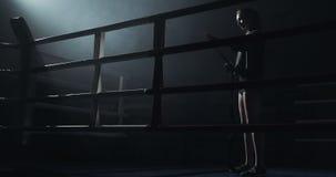 Junge Frau, die Hände mit schwarzen boxenden Verpackungen im dunklen Ring einwickelt Schattenbild Verpackenkonzept stock footage