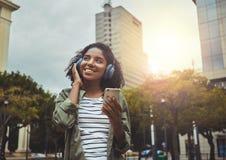 Junge Frau, die hörende Musik auf Kopfhörer genießt lizenzfreie stockfotografie
