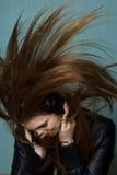 Junge Frau, die Haar beim Hören Musik wirft Stockbild
