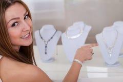 Junge Frau, die Halskette betrachtet stockbilder