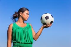 Junge Frau, die an Hand Fußball mit blauem Himmel hält lizenzfreie stockbilder