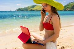 Junge Frau, die am Handy bei der Anwendung einer Tablette auf dem Strand spricht Stockbild