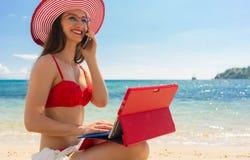 Junge Frau, die am Handy bei der Anwendung einer Tablette auf dem Strand spricht Lizenzfreies Stockbild