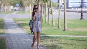 Junge Frau, die am Handy beim Gehen in Park spricht stock video footage