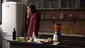 Junge Frau, die am Handy beim Kochen spricht stock footage