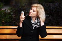 Junge Frau, die Handy betrachtet Stockfotos