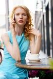 Junge Frau, die am Handy in einem Café spricht Stockfotografie
