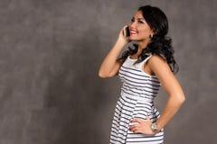 Junge Frau, die am Handy gegen grauen Hintergrund spricht stockbilder