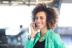 Junge Frau, die Handy im Büro verwendet Stockfotografie