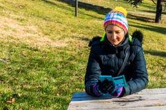 Junge Frau, die am Handy im Park simst Lizenzfreie Stockfotografie