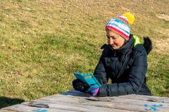Junge Frau, die am Handy im Park simst Lizenzfreie Stockbilder