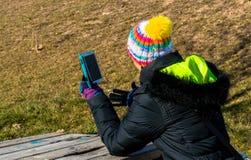 Junge Frau, die am Handy im Park simst Lizenzfreies Stockfoto