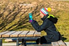 Junge Frau, die am Handy im Park spricht Stockbilder