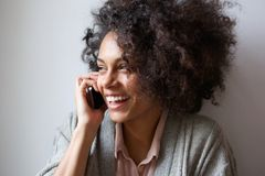 Junge Frau, die am Handy lacht und spricht Lizenzfreies Stockbild