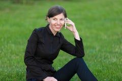 Junge Frau, die am Handy sitzt auf Gras spricht Lizenzfreie Stockfotos
