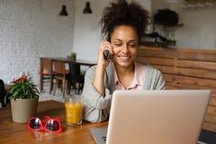 Junge Frau, die Handy verwendet und an Laptop arbeitet lizenzfreies stockbild