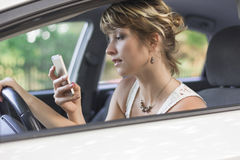 Junge Frau, die Handy während Autofahren verwendet Lizenzfreie Stockfotografie