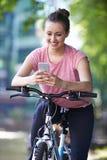 Junge Frau, die Handy während heraus auf Zyklus-Fahrt verwendet stockfoto