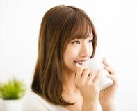 Junge Frau, die heißen Lattekaffee trinkt Stockfoto