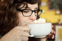 Junge Frau, die an heißer Schokolade nippt Stockbild