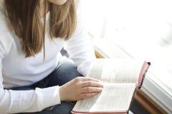 Junge Frau, die heilige Bibel liest Stockbild