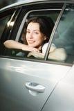 Junge Frau, die heraus das Autofenster schaut Lizenzfreie Stockfotografie