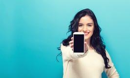 Junge Frau, die heraus ein Mobiltelefon hält stockfoto