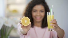 Junge Frau, die heraus orange halten und Glas Saft und, reich in den Vitaminen, die lächeln stock video footage