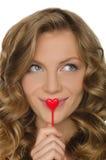 Junge Frau, die Herz in der vorderen Lippe hält Lizenzfreie Stockbilder