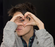 Junge Frau, die Herz mit den Fingern auf Schwarzem formt Stockfotos