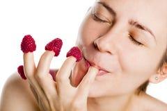Junge Frau, die Himbeeren von den Fingern isst. Stockbilder