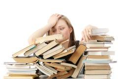 Junge Frau, die hinter Büchern sitzt Lizenzfreies Stockbild