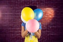 Junge Frau, die hinter Ballonen sich versteckt Lizenzfreie Stockfotografie
