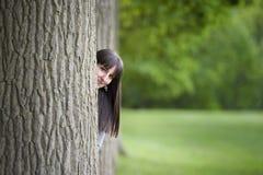 Junge Frau, die hinter einem Baum sich versteckt Stockbilder