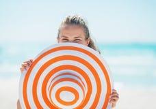 Junge Frau, die hinter Hut auf Strand sich versteckt Lizenzfreie Stockfotos