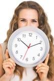 Junge Frau, die hinter Uhr sich versteckt Lizenzfreies Stockfoto